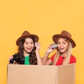 Bambina con cappello giocando in scatola di cartone animato