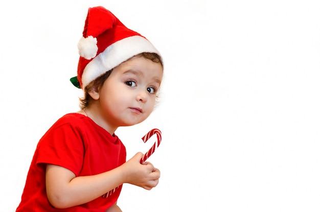 Bambina con cappello santa mangia un bastoncino di zucchero con appetito, sembra astutamente. dolci natalizi e regali per bambini.