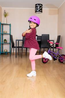 Bambina con casco da bicicletta felice perché andrà in bicicletta a casa