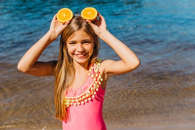 Bambina con fette d'arancia facendo orecchie sulla spiaggia
