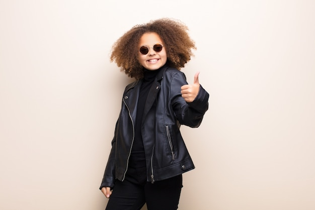 Bambina con giacca di pelle e occhiali da sole