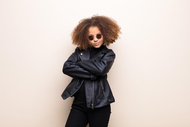 Bambina con giacca di pelle nera e occhiali da sole