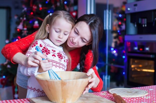 Bambina con i biscotti di pan di zenzero di natale di cottura della giovane madre insieme