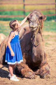 Bambina con i cammelli nello zoo il giorno di estate caldo e soleggiato. svago attivo per la famiglia.