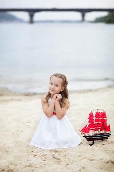 Bambina con i capelli biondi in abito bianco azienda nave con vele scarlatte. il bambino si siede in riva al mare, tiene in mano una barca a vela giocattolo.