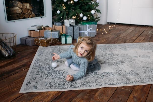 Bambina con i contenitori di regalo e l'albero di natale su fondo