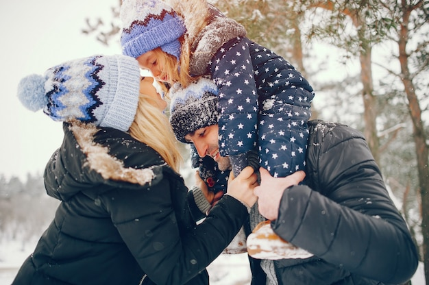 Bambina con i genitori che giocano in un parco d'inverno
