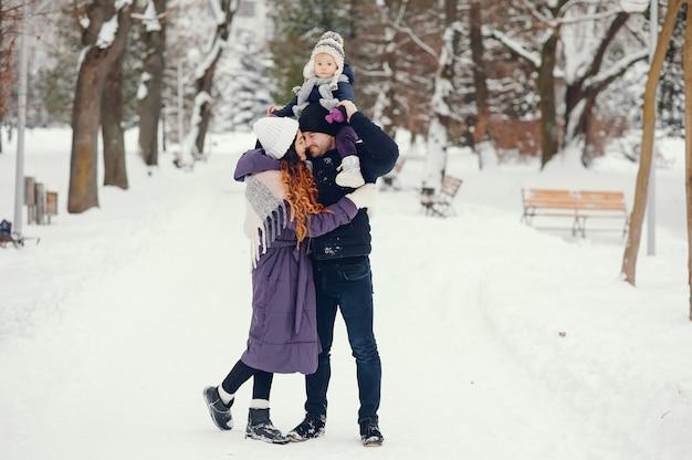 Bambina con i genitori in un parco di inverno