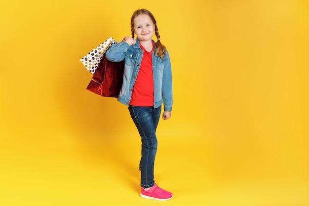 Bambina con i sacchetti su una priorità bassa gialla