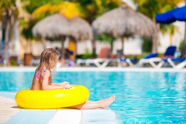 Bambina con il cerchio di gomma gonfiabile nella piscina