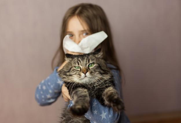 Bambina con il tessuto e l'animale domestico su fondo. concetto di allergie ai gatti