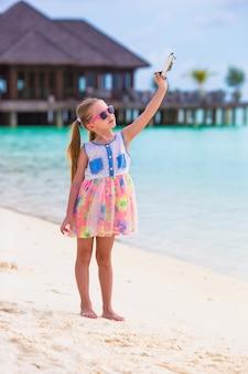 Bambina con l'aeroplano giocattolo nelle mani sulla spiaggia di sabbia bianca