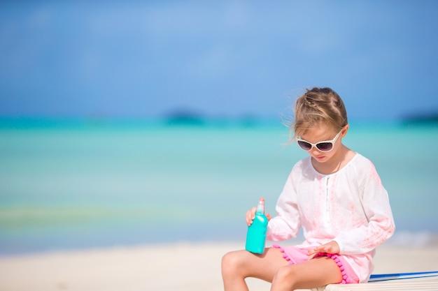 Bambina con la bottiglia di crema solare che si siede alla spiaggia tropicale