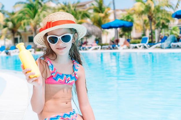 Bambina con la bottiglia di crema solare in piscina