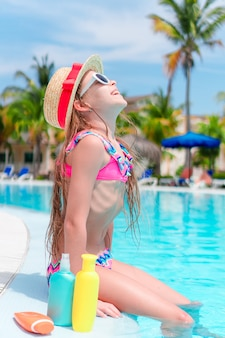 Bambina con la bottiglia di crema solare seduto sul bordo della piscina