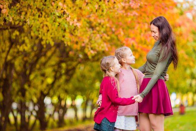 Bambina con la mamma all'aperto nel parco al giorno di autunno