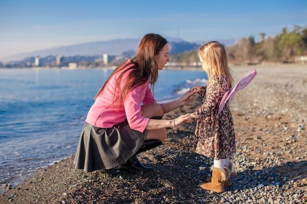 Bambina con la mamma divertirsi sulla spiaggia in una giornata invernale
