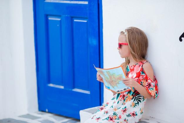 Bambina con la mappa dell'isola all'aperto in vecchie strade un mykonos.