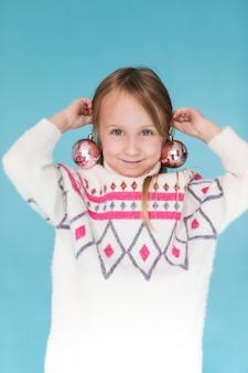 Bambina con la palla di natale come orecchini