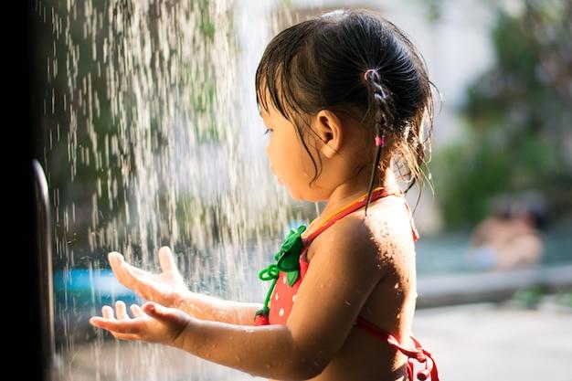 Bambina con la testa di doccia all'aperto per nuotare