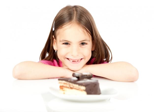 Bambina con la torta di cioccolato isolata su bianco