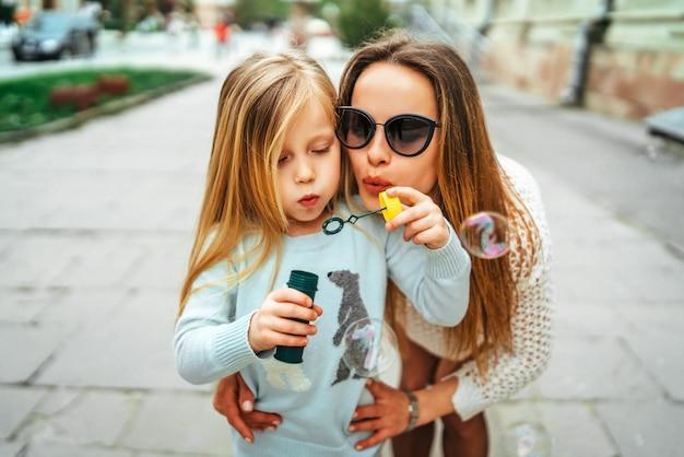 Bambina con le bolle di salto della madre all'aperto