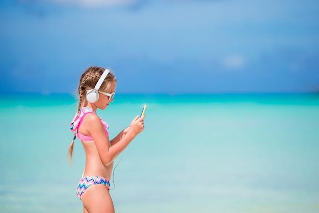 Bambina con le cuffie sulla spiaggia