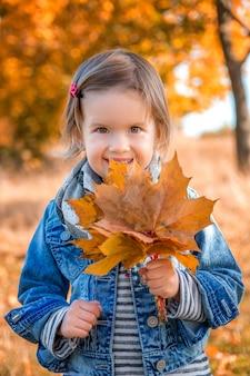 Bambina con le foglie dorate di autunno giallo. gioco da bambini all'aperto nel parco. ritratto. contento.