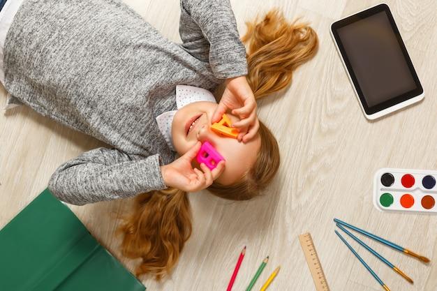Bambina con le lettere a e b disteso sul pavimento.