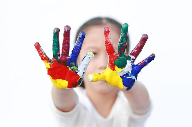 Bambina con le mani verniciate colorate
