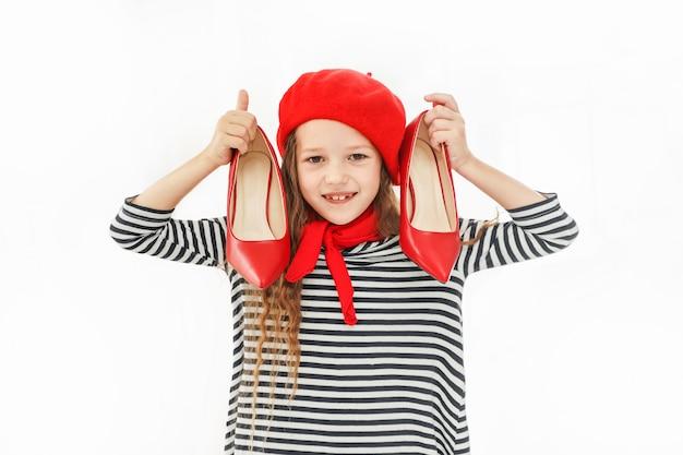 Bambina con le scarpe rosse in mano.