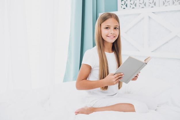 Bambina con libro guardando la telecamera