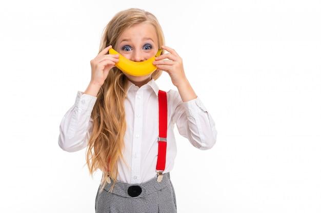 Bambina con lunghi capelli biondi in camicia bianca, pull-up rossi, pantaloni in gabbia, calzini rossi e scarpe con trucco luminoso con banana