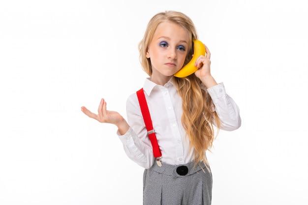 Bambina con lunghi capelli biondi in camicia bianca, pull-up rossi, pantaloni in gabbia, calzini rossi e scarpe con trucco luminoso e banana