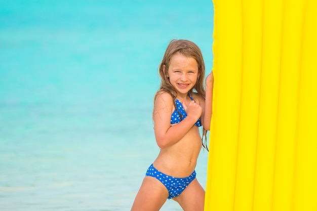 Bambina con materasso ad aria in vacanza estiva in spiaggia tropicale