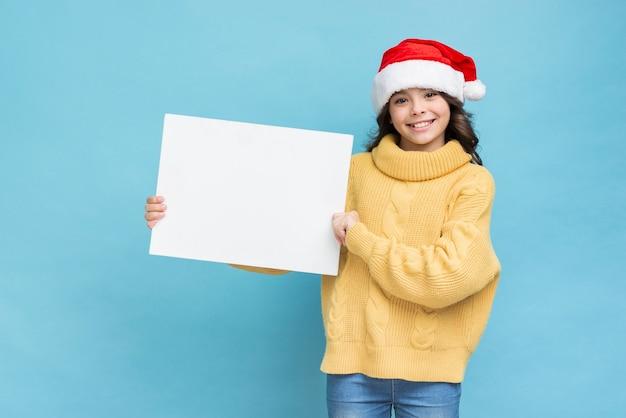Bambina con mockup di poster nelle mani