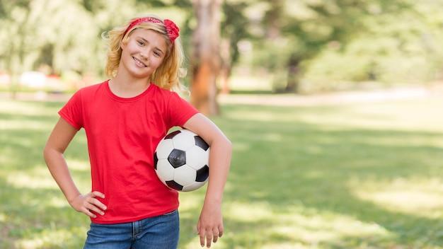 Bambina con pallone da calcio alla pari