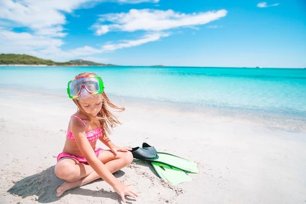 Bambina con pinne e occhiali per lo snorkeling sulla spiaggia