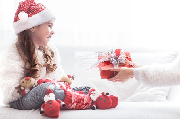Bambina con regalo di natale in costume di babbo natale