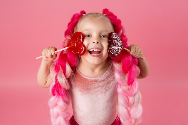 Bambina con trecce di kanekalon rosa detiene una lecca-lecca a forma di cuore su uno sfondo rosa
