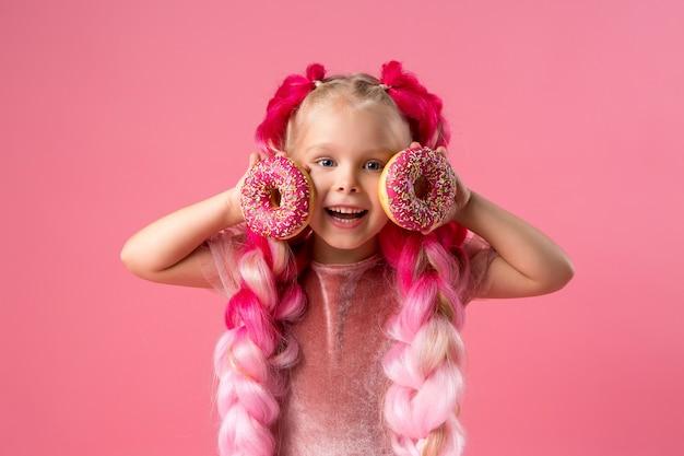 Bambina con trecce kanekalon con ciambelle su sfondo rosa