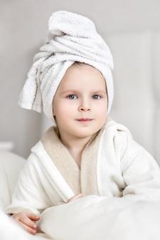 Bambina con un asciugamano bianco in testa