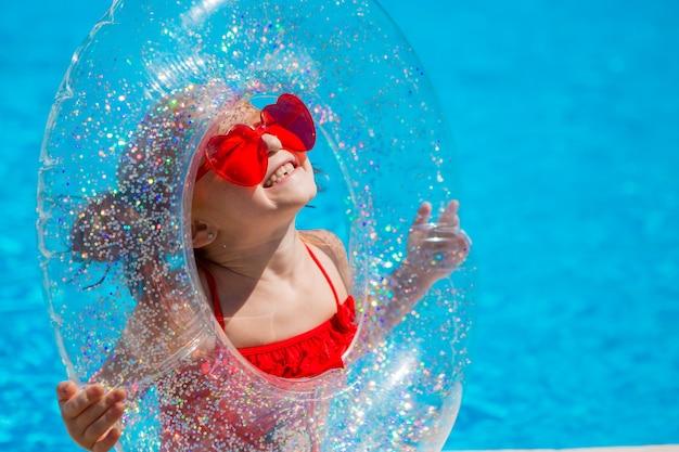 Bambina con un cerchio di nuoto in piscina