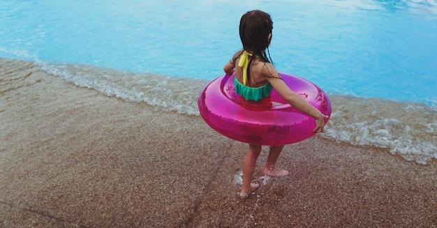 Bambina con un galleggiante estivo in piscina