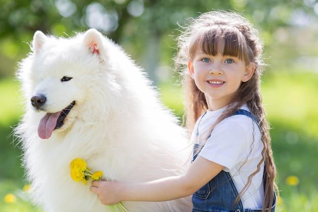 Bambina con un grande cane bianco nel parco.