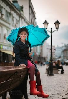 Bambina con un ombrello in stivali di gomma divertirsi su una panchina nel centro di mosca