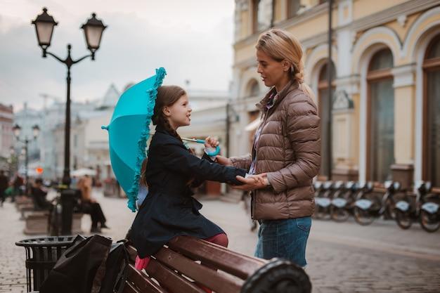 Bambina con un ombrello in stivali di gomma si diverte con sua madre su una panchina nel centro di mosca