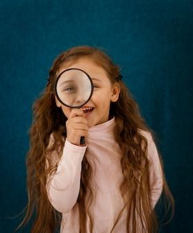 Bambina con una lente d'ingrandimento