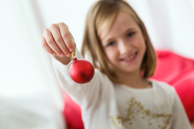 Bambina con una palla di natale rossa in mano