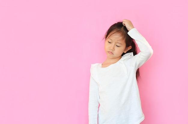 Bambina confusa graffiando la sua testa su sfondo rosa